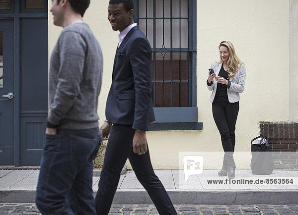Junge Menschen im Frühling auf den Straßen der Stadt im Freien. Eine allein stehende Frau und zwei Männer  die auf der gepflasterten Straße vorbeigehen.