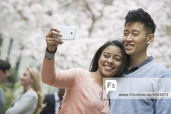 Stadtleben im Frühling. Jugendliche im Freien in einem Stadtpark. Ein Paar beim Selbstporträt oder Selbstporträt mit einem Smartphone.