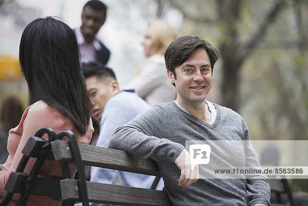 Stadtleben im Frühling. Jugendliche im Freien in einem Stadtpark. Sitzen auf einer Parkbank. Ein Mann lächelt in die Kamera. Vier Menschen im Hintergrund.