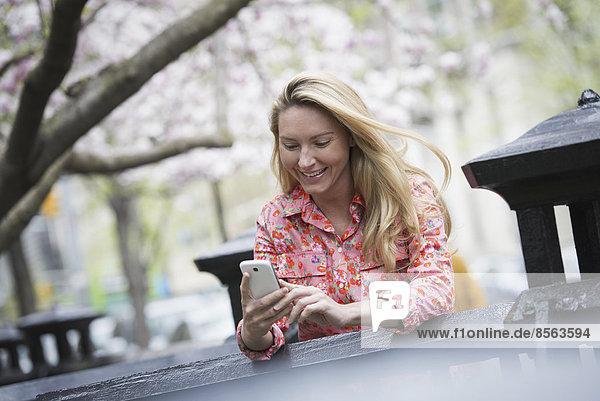 Stadtleben im Frühling. Eine junge Frau mit langen blonden Haaren sitzt in einem Stadtpark und schaut auf ihr Smartphone.