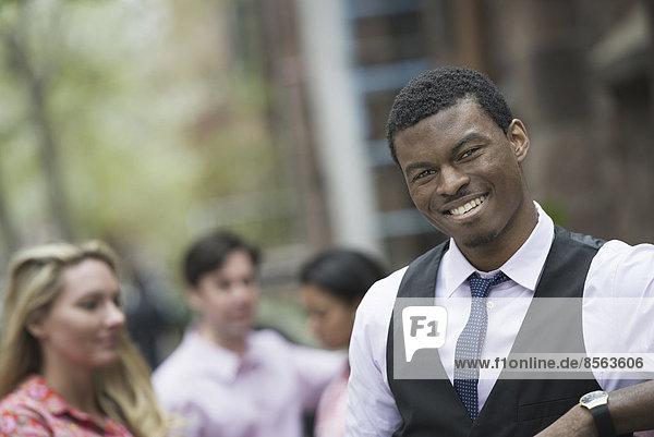 hinter  Außenaufnahme  Mann  Mensch  Lifestyle  Menschen  lächeln  Großstadt  Blick in die Kamera  jung  3  freie Natur