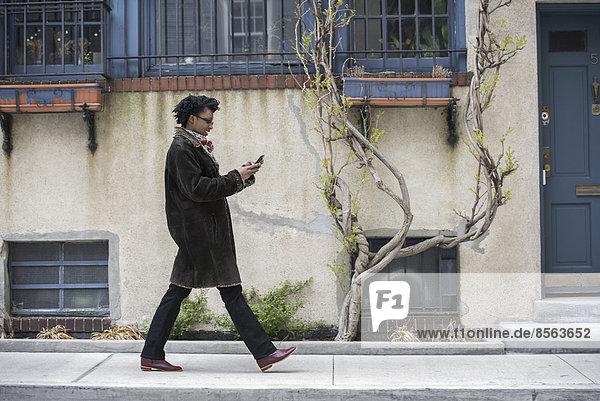 Eine Frau in einem warmen Mantel geht die Straße entlang und überprüft ihr Telefon.