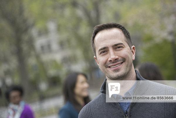Eine Gruppe von Menschen in einem Stadtpark. Ein Mann in einem grauen Pullover  lächelnd.