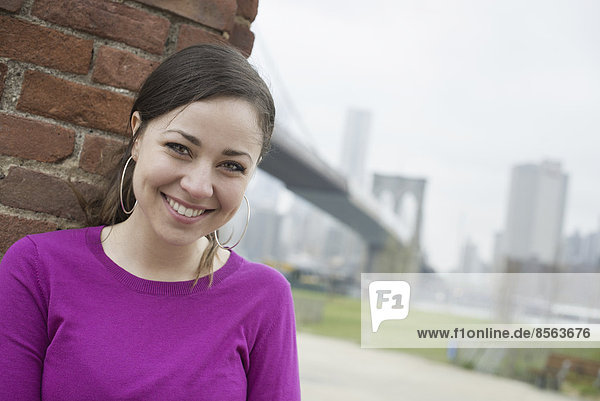 New York City  die Brooklyn Bridge  die über den East River führt. Eine Frau sitzt an eine Ziegelmauer gelehnt und überprüft ihr Smartphone.