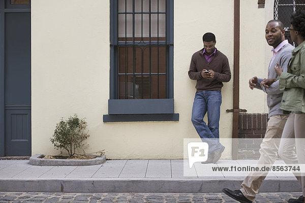 Draußen in der Stadt im Frühling. Ein Paar  das auf dem Bürgersteig geht  und ein Mann  der an einer Wand lehnt und sein Telefon überprüft.
