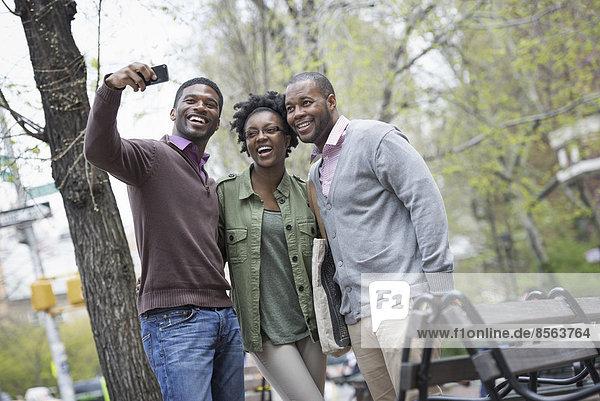 Draußen in der Stadt im Frühling. Ein urbaner Lebensstil. Drei Menschen posieren zusammen und einer macht ein Foto von ihnen mit einem Smartphone.