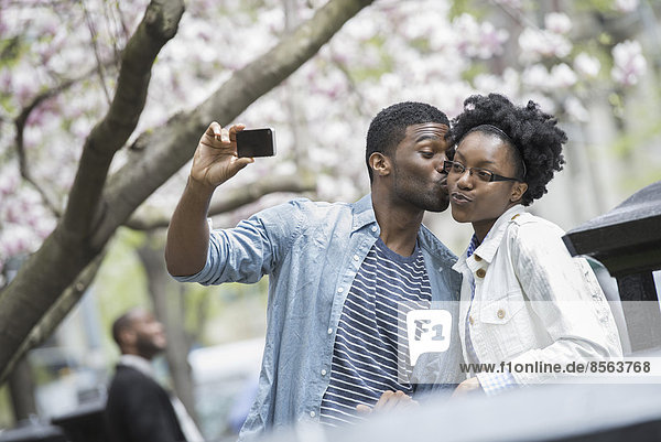 Outdoors in the city in spring. An urban lifestyle. A man kissing a woman and taking a photograph with a handheld mobile phone.
