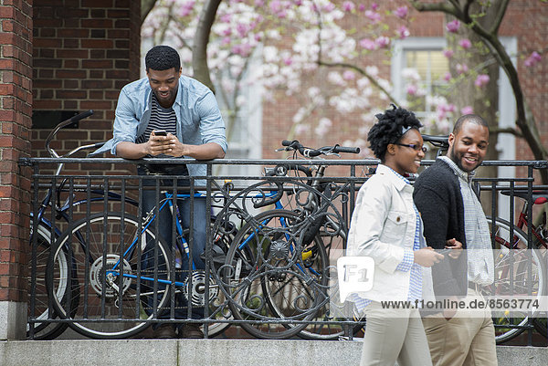 A bicycle rack with locked bicycles  a man texting and a couple walking by.