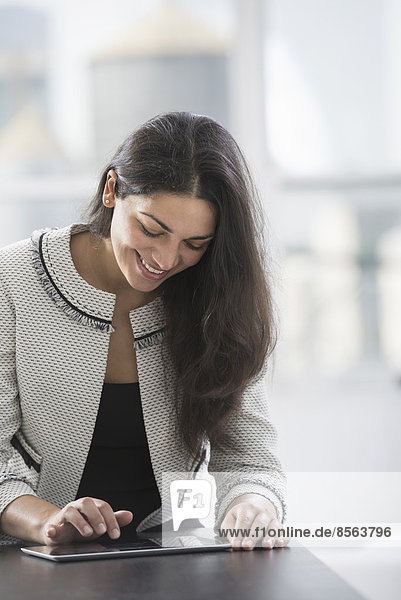 Young professionals at work. A woman at a work table using a digital tablet.