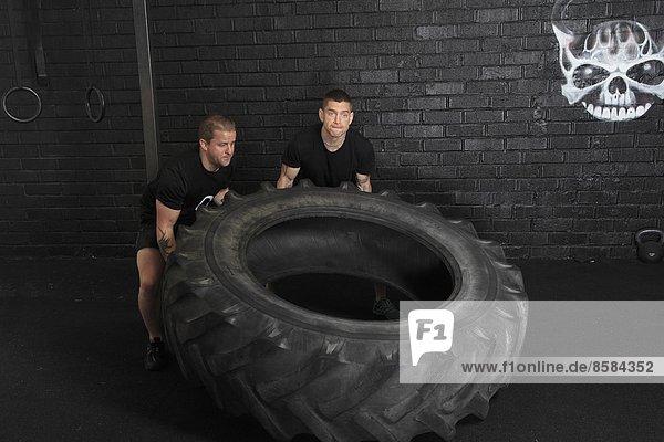 Frankreich  zwei Männer  die ein Rad in einer Crossfit-Turnhalle bewegen.