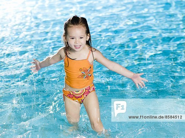 Little girl playing with water at the swimming pool