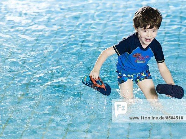 Junge spielt mit seinen Sandalen im Schwimmbad
