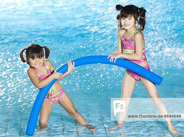 Two grils playing with pool noodle