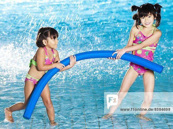 Two girls playing with pool noodles