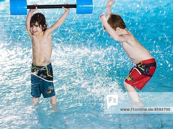 Two boys splashing at the swimming pool