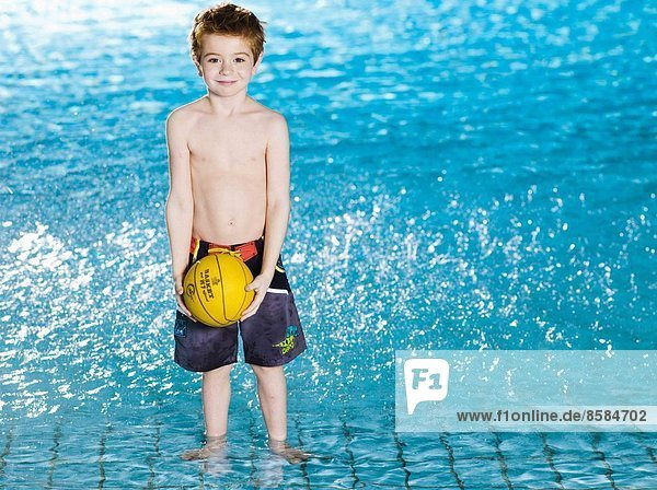 Little boy with ball at the swimming pool