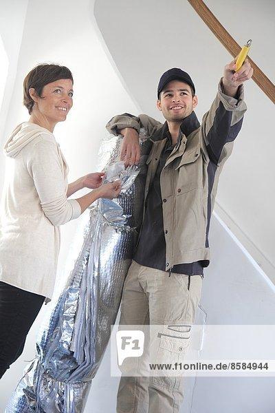 Frankreich  Frau und Arbeiter diskutieren über die thermische Isolation des Hauses.