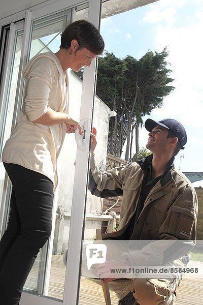 Frankreich  Besitzer und Mann diskutieren vor einem Fenster.