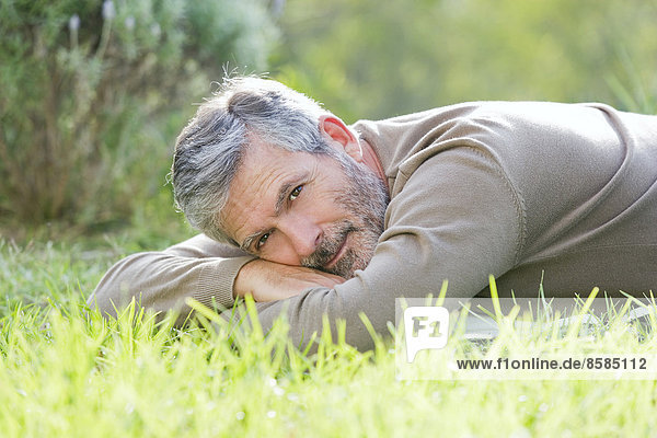 Mature man laying on the grass