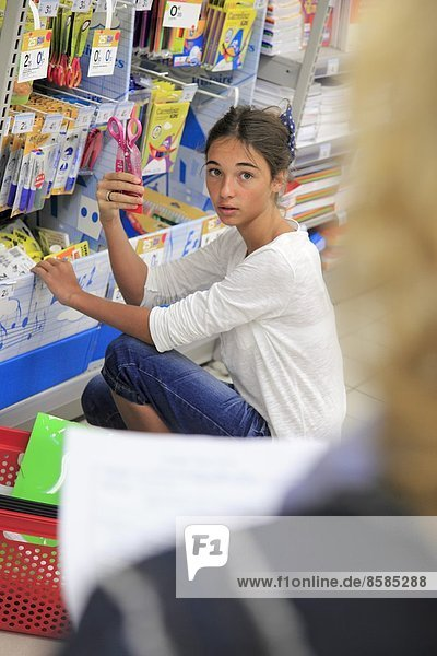 France  young girl in a supermarket  shopping for school.