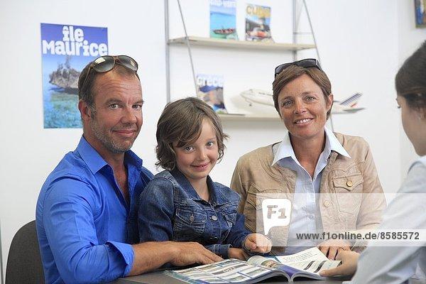 Frankreich  Familie im Reisebüro.
