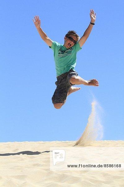 Spanien  Kanarische Inseln. Kleiner Junge  der an einem Sandstrand spielt.