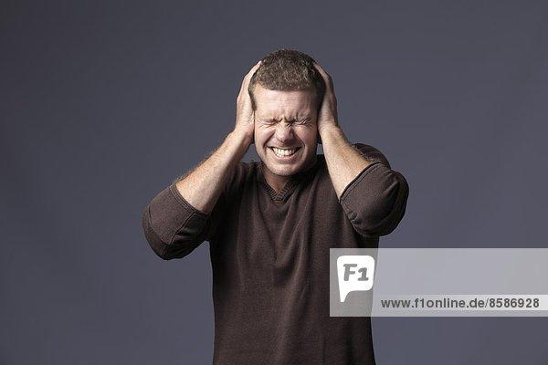 Frankreich  junger Mann auf grauem Grund  der die Ohren hält.