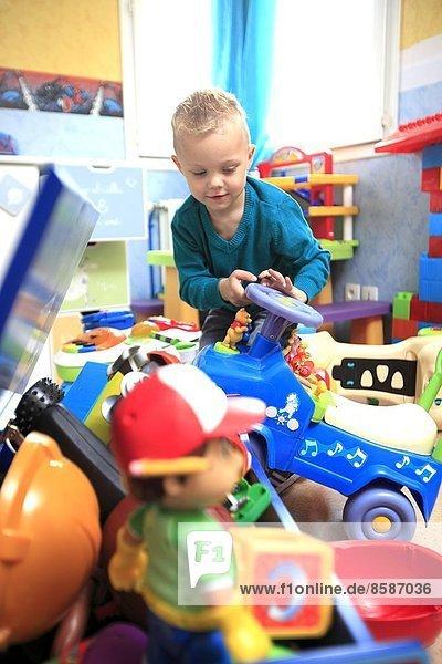 Frankreich  kleiner Junge in seinem Zimmer voller Spielzeug.