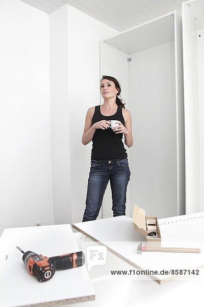 Frankreich  junge Frau baut einen Schrank.