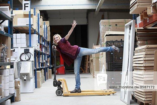 Frankreich  junge Frau mit Transpallet im Lagerhaus.