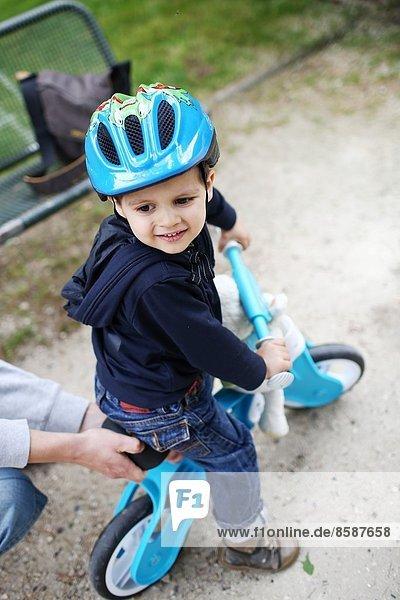 Ein kleiner Junge und sein Fahrrad im Park