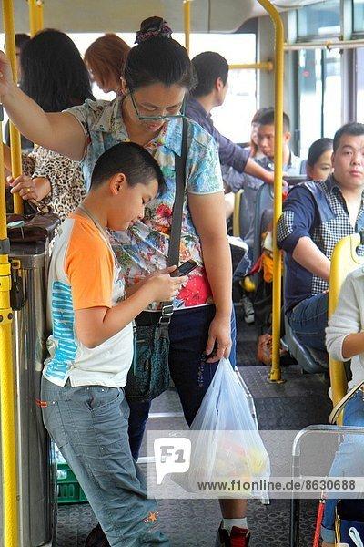 stehend  benutzen  Frau  Mann  sehen  Kurznachricht  Junge - Person  Sohn  fahren  Öffentlicher Verkehr  Passagier  Omnibus  Peking  Hauptstadt  China  Mutter - Mensch  Smartphone