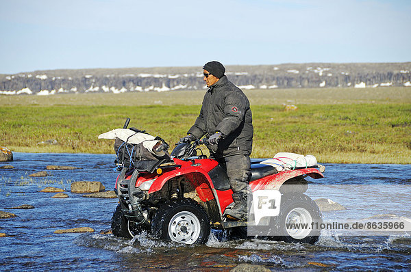 Man of the Inuit people riding a quad bike  ATV  through a river in the tundra on Victoria Island  formerly Holman Island  village of Ulukhaktok  Northwest Territories  Canada