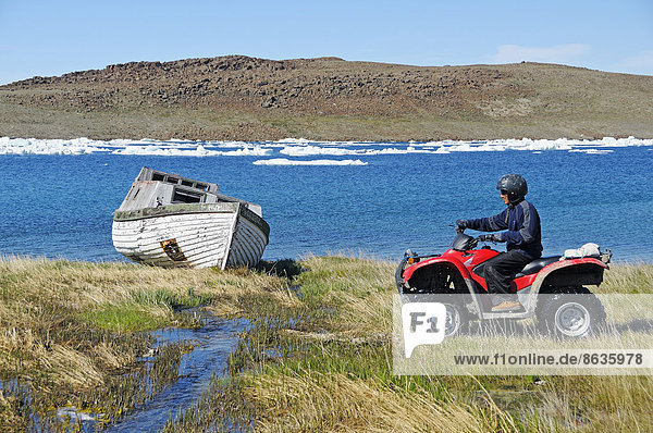 Man of the Inuit people riding a quad bike  ATM  in the tundra to Victoria Island  formerly Holman Island  village of Ulukhaktok  Northwest Territories  Canada