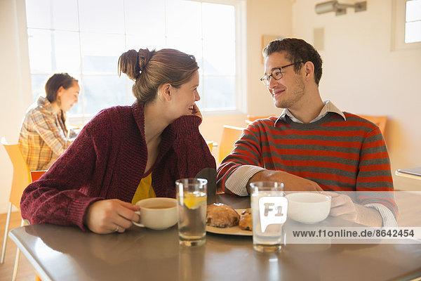 Zwei junge Leute  ein Mann und eine junge Frau  sitzen an einem Tresen in einem Café.