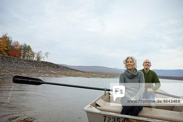Ein Paar  Mann und Frau  die an einem Herbsttag in einem Ruderboot auf dem Wasser sitzen.