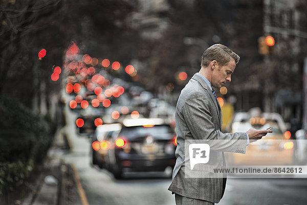 Ein Mann in einem Anzug  der sein Mobiltelefon überprüft  steht in der Abenddämmerung auf einer belebten Straße.