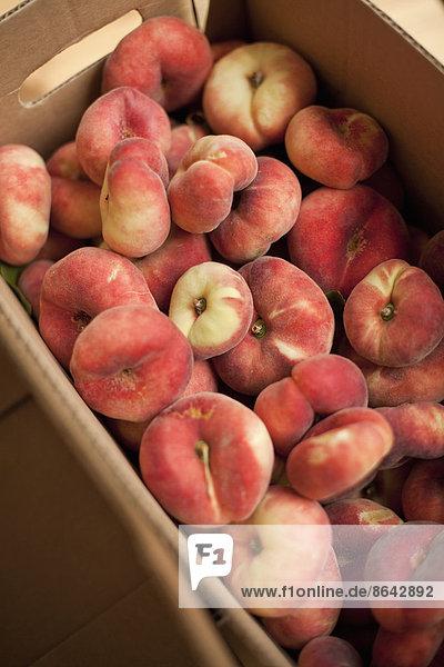 Frisches Obst am Stand eines Biobetriebs. Doughnut-Pfirsiche in einer Kiste.