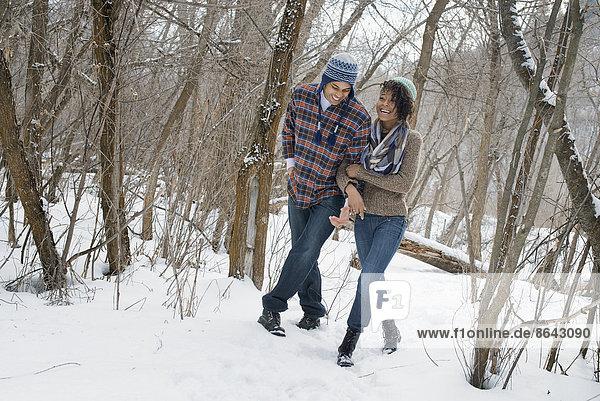 Winterlandschaft mit Schnee auf dem Boden. Ein Paar  das Arm in Arm durch den Wald geht.