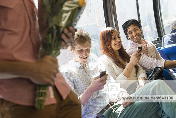 Urbaner Lebensstil. Eine Gruppe von Menschen  Männer und Frauen  in einem Stadtbus in New York City. Zwei Personen überprüfen ihre Telefone. Ein Mann steht mit einem Blumenstrauß in der Hand.