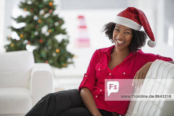 Weihnachtsmann sitzend Frau Couch Baum Hut weiß Dekoration rot Kleidung