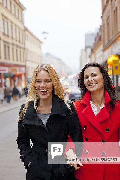 Two female friends walking together in street