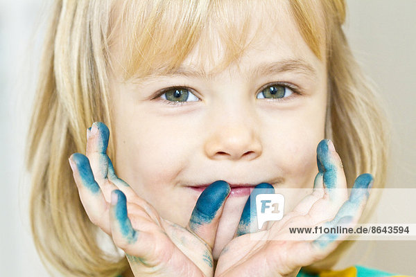 Blondes Mädchen mit Farbe an den Händen  Portrait