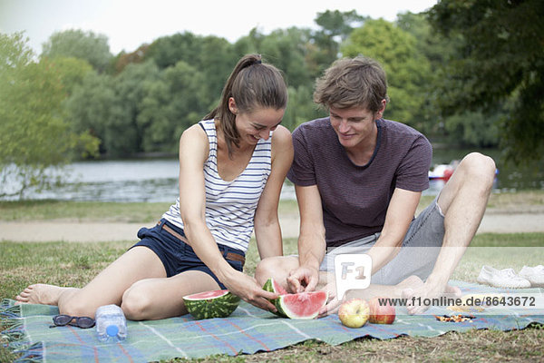Junges Paar beim Picknick  Wassermelone schneiden