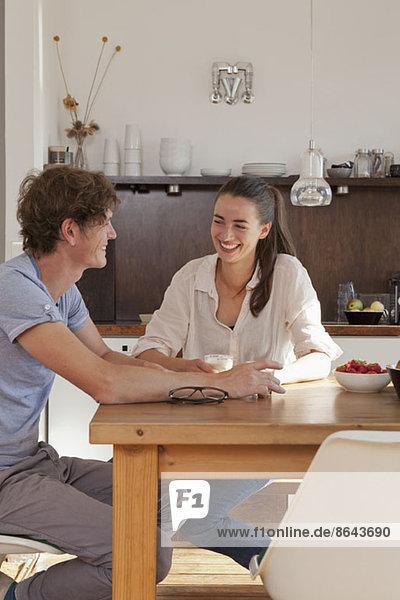 Junges Paar am Esstisch in der Küche sitzend