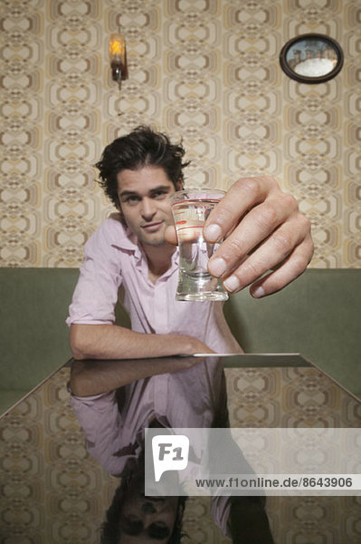 Ein Mann  der mit einem Schnapsglas anstoßen will.
