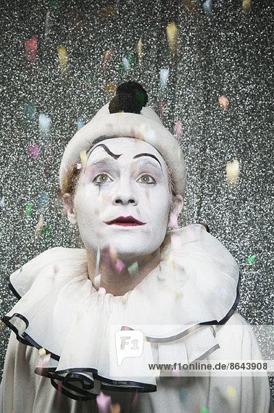 Ein Clown  der Konfetti auf die Bühne fallen sieht