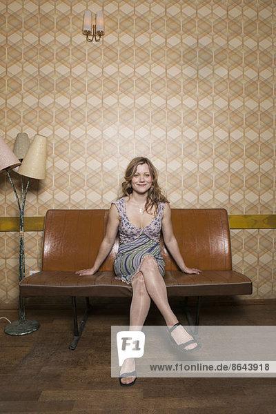 Eine lächelnde Frau  die in einem Zimmer im Retro-Stil sitzt.