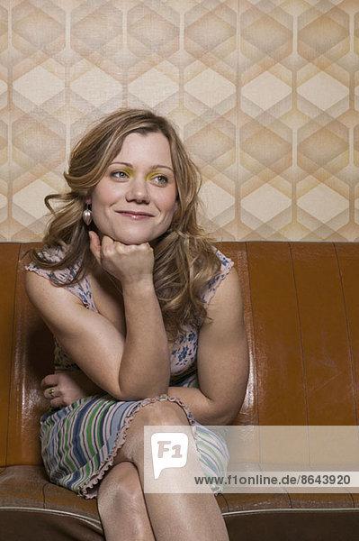 Eine lächelnde Frau sitzt auf dem Sofa und schaut weg.