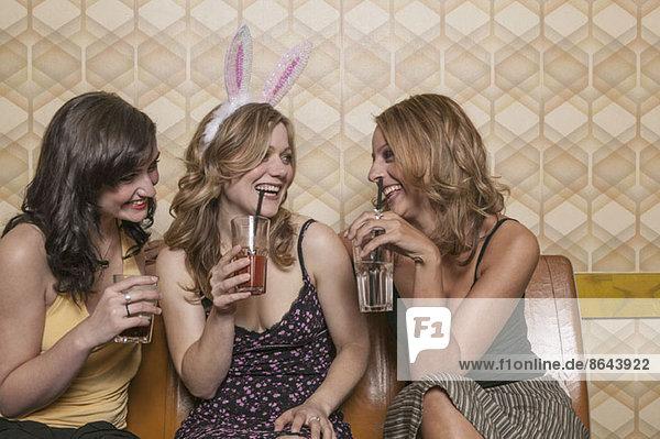 Drei Frauen  die zusammen Cocktails trinken